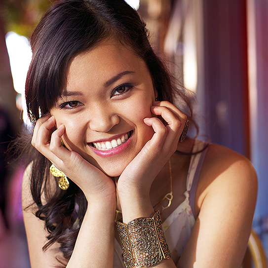 young woman smiling with head resting in her palms