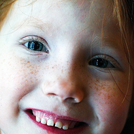 little girl with freckles smiling