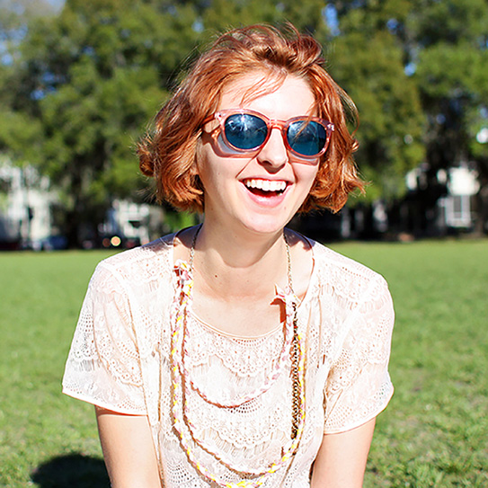 girl smiling while wearing sunglasses