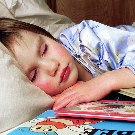 little girl sleeping next to coloring books