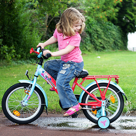 little girl riding bike with training wheels