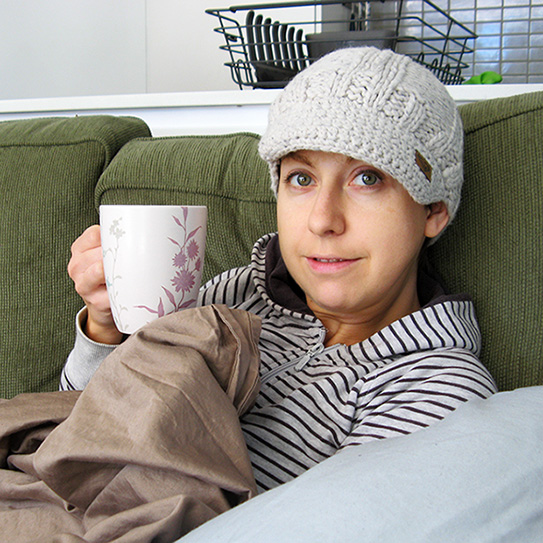 woman wearing beanie on couch and holding coffee mug