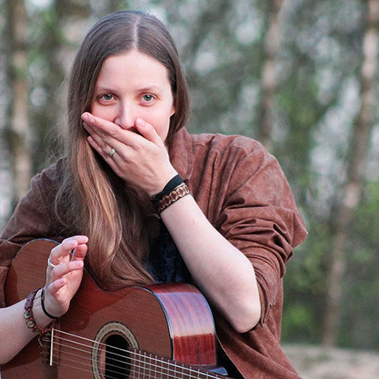 woman using guitar and covering her mouth