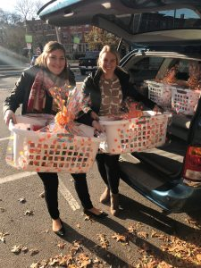 two woman taking thanksgiving baskets out of car