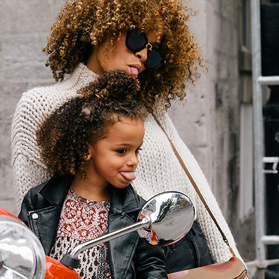 woman and daughter dressed chic sitting on scooter outside