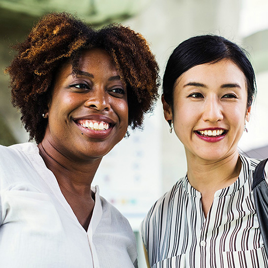 two woman smiling together