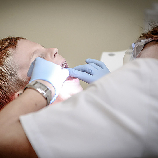 child getting mouth checked by dentist