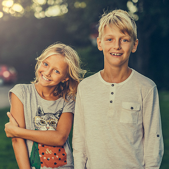 girl and boy smiling in yard