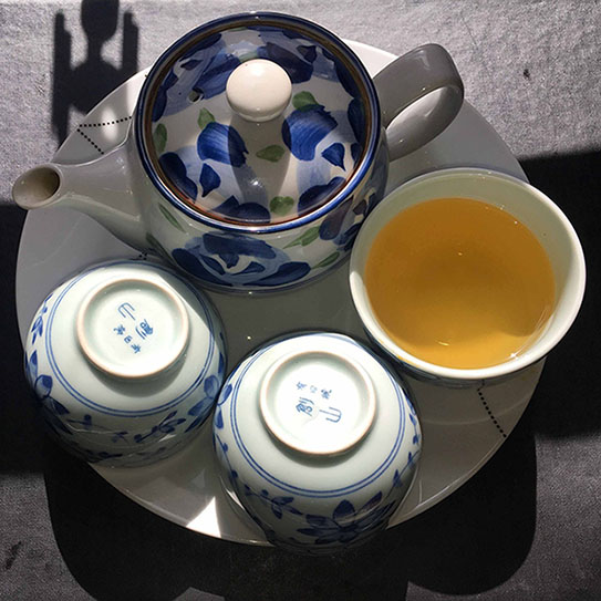 Green tea in a cup and a blue pot
