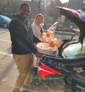 A man and a woman loading packages into the trunk of a car