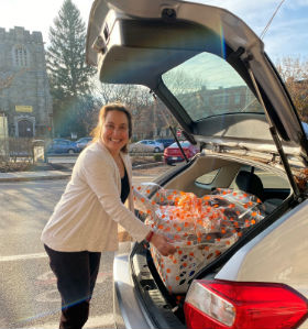 A woman loading goodies into the back of a car