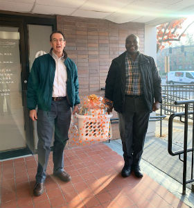 Two men carrying a basket