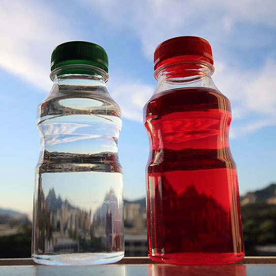 bottle of red juice next to a bottle of water