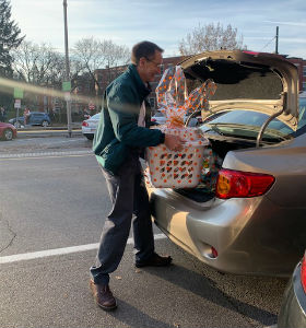 A man loading baskets into the trunk of a car