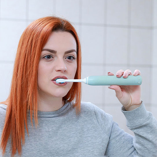 young woman using electric toothbrush