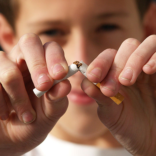 Young kid breaking a cigarette