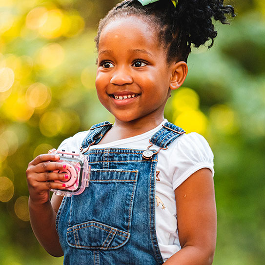young girl in overalls smiling