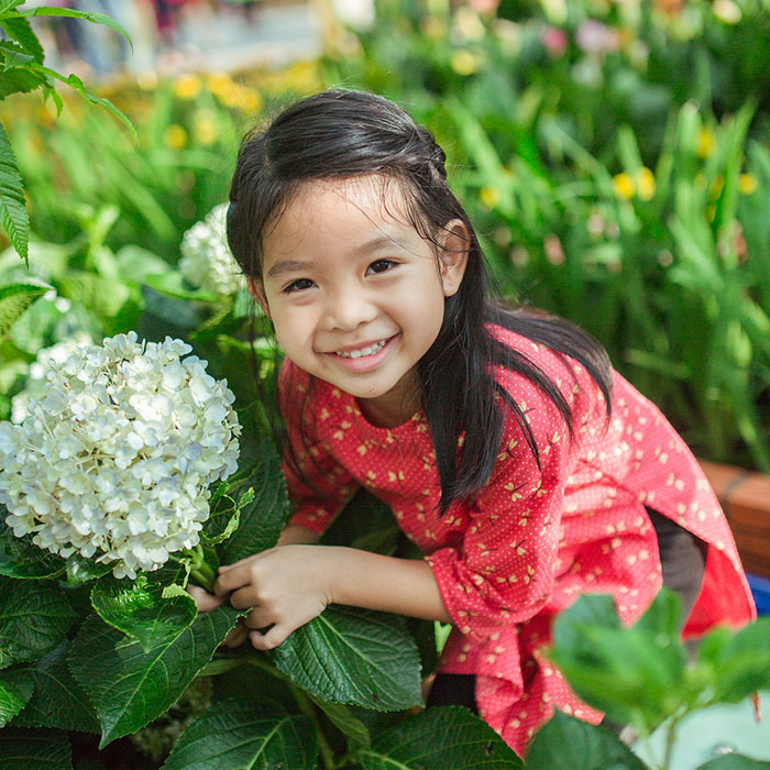 little girl smiling with a white flower