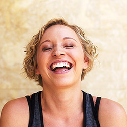 woman with eyes closed smiling