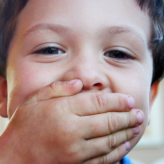 little boy with hand over mouth