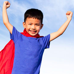 boy with superhero cape and arms up