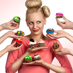 blonde woman surrounded by hands holding cupcakes