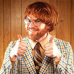 man in checkered suit, smiling and giving thumbs up