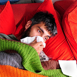 man sick in bed, blowing nose