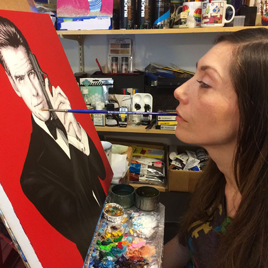 woman with paintbrush in mouth looking at canvas