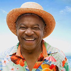 65 year old man in tropical vacation attire smiling
