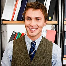 man smiling in front of book shelf
