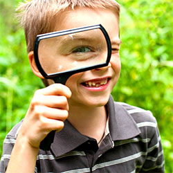 little boy using magnifying glass