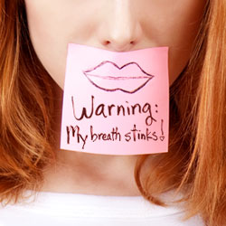 woman with a sign that reads warning my breath stinks