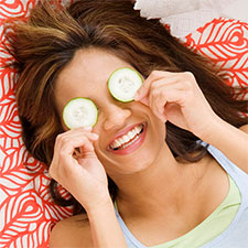 woman smiling with cucumbers on her eyes