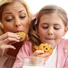 mom and daughter eating milk and cookies